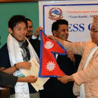Japanese climber Nobokazu Kuriki accepts his permit to climb Everest, and a Nepalese flag, from Nepal's tourism minister, Kripasur Sherpa, in Kathmandu on Sunday. Hundreds of climbers had to abandon their attempts when an earthquake-triggered avalanche struck Everest base camp in April, marking a second year with virtually no summits after the deaths of 16 Nepalese guides in 2014 sparked a shutdown of the world's highest peak. The mountain has been reopened to climbers and Kuriki will be the first to attempt reaching the summit. | AFP-JIJI