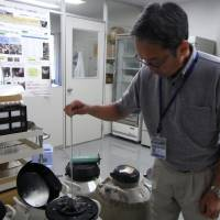 Noriyoshi Ichikawa, director of the Preservation and Research Center in Yokohama, pulls up tubes of frozen reproductive cells from a tank. | MIZUHO AOKI