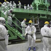 Members of the media and Tokyo Electric Power Co. employees view a fuel-handling machine after seeing the spent fuel pool inside the building housing reactor 4 at the Fukushima No. 1 nuclear power plant in Okuma, Fukushima Prefecture, in November 2013. | AP