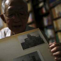 Hiroshima A-bomb survivor Akira Yamada, 89, shows a photo of the Atomic Bomb Dome during an interview in Fukushima on July 30. Yamada heads a group of survivors in the prefecture. | REUTERS