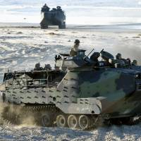 An AAV-7 amphibious vehicle makes its way across a beach during a joint drill involving the U.S. Marine Corps and the Ground Self-Defense Force at Camp Pendleton in California on Feb. 25. The war game mimicked the retaking of a remote island. | KYODO