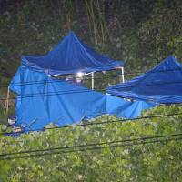 Investigators probe the area in which the body of Ryoto Hoshino was found in Kashiwara, Osaka Prefecture, at 9:47 p.m. on Friday.   KYODO