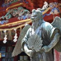 A statue of a long-nosed goblin stands in front of Yakuo-in Temple. The demon-like being is believed to be a denizen of Mount Takao. | SATOKO KAWASAKI