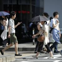 Women use parasols to shelter from the sun as they cross a street in Tokyo on July 13. | BLOOMBERG