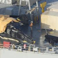 The U.S. Army H-60 is seen with its tail ripped off after crash landing on  the USNS Red Cloud naval cargo ship in international waters off Okinawa Prefecture on Wednesday. | KYODO