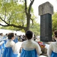 Women wearing traditional Korean costumes sing a requiem in Hiroshima on Wednesday, in front of a monument bearing the names of Korean atomic bomb victims. | KYODO