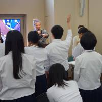 High school students get a taste of the New York-based Hibakusha Stories project on Aug. 6 at Hiroshima Jogakuin Junior & Senior High School in Hiroshima, with project members Robert Croonquist (right) and Kathleen Sullivan (left) conducting an introductory presentation. | KYODO