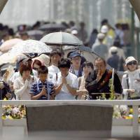 Mourners pray before the cenotaph for the victims of the 1945 atomic bombing, at Peace Memorial Park in Hiroshima on Thursday. A bell tolled and thousands bowed their heads in prayer at the time the bomb struck.  | REUTERS