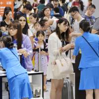 Travelers line up at check-in counters for flights on low-cost carriers Saturday at Narita airport. | KYODO
