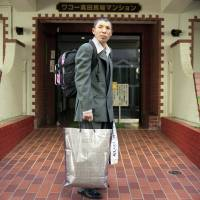A homeless man, wearing a donated suit, is ready to return to his hometown from Tokyo in 2007.   COURTESY OF HIDEAKI TAKAMATSU / KYODO