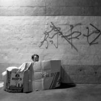 A homeless man lives in a shelter made of cardboard boxes in Fuchu, Tokyo, in 1997, after giving up on jobs with poor working conditions in construction.   COURTESY OF HIDEAKI TAKAMATSU / KYODO