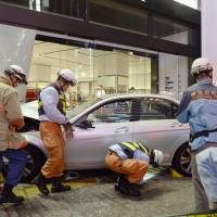 Firefighters inspect the scene of a deadly car crash near JR Ikebukuro Station in Tokyo on Sunday night after the car plowed into pedestrians and smashed into a storefront. | KYODO