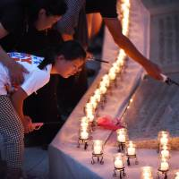 Relatives of the 1985 Japan Airlines jumbo jet crash victims light candles during a memorial ceremony in the village of Ueno, Gunma Prefecture, on Wednesday, the 30th anniversary of the disaster. | AFP-JIJI