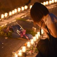 A woman prays for the 1985 Japan Airlines crash victims at a candlelight vigil on Wednesday evening in the village of Ueno, Gunma Prefecture, on the 30th anniversary of the tragedy. | AFP-JIJI