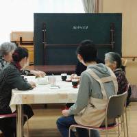 A teenage parolee takes part in community service at a Fukui Prefecture welfare facility in April 2014. The handout image has been blurred by the provider. | COURTESY OF JUSTICE MINISTRY / KYODO
