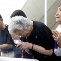 People pray for victims of the 1945 atomic bombing in front of the Peace Statue at Nagasaki's Peace Park on Sunday. | REUTERS