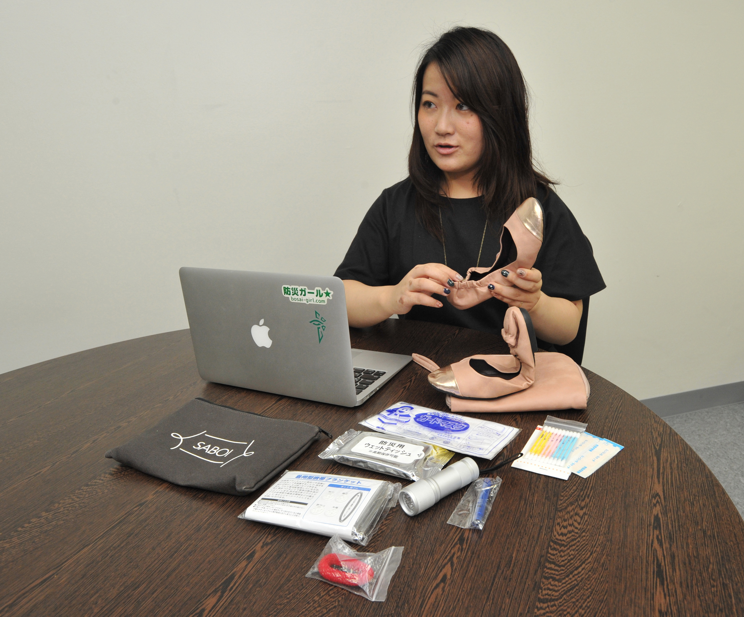 Bosai Girl founder Misaki Tanaka shows disaster-preparedness goods under the SABOI brand during an interview in July at the group's office in Tokyo's Shibuya Ward. | YOSHIAKI MIURA
