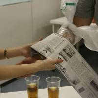 Female and male participants learn how to stop bleeding using daily commodities at a Bosai Machikon mixer in Tokyo in July 2014.   BOSAI GIRL