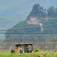 Military guard posts of North Korea (top) and South Korea are seen close to each other near the South Korean border city of Paju on Friday.   AFP-JIJI