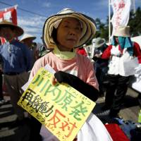 A protester attends a rally Tuesday outside of Kyushu Electric Power Co.'s Sendai nuclear plant in Satsumasendai, Kagoshima Prefecture. Her sign reads 'Against restart at Sendai nuclear power station.' | REUTERS