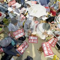 People stage a sit-in in front of the Kyushu Electric Power Co. nuclear plant in Satsumasendai, Kagoshima Prefecture, on Tuesday morning, prior to the restart of its No. 1 reactor. | KYODO