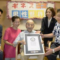 Yasutaro Koide (center) is celebrated in Nagoya on Friday after he was recognized as the world's oldest living male by the Guinness World Records. Asked by Nagoya Mayor Takashi Kawamura (far right) what the key to his longevity is, the 112-year-old said it was taking things easy. | KYODO