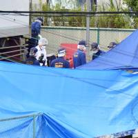 Investigators on Friday scour the site where the body of a girl was found in Takatsuki, Osaka Prefecture, a day earlier. | KYODO