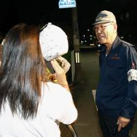 A member of Neyagawa's crime prevention association talks to children walking on the street in Osaka Monday night. | KYODO