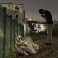 A man prays late Friday at the site where the body of 13-year-old Natsumi Hirata was found Aug. 13 in Takatsuki, Osaka Prefecture. | KYODO