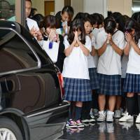 Schoolmates of Natsumi Hirata pray for the slain girl as the hearse carrying her body leaves a funeral home in Neyagawa, Osaka Prefecture, on Saturday. | KYODO