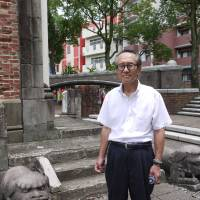 Shigeyuki Anan poses on July 29 in front of bricks that used to be part of Urakami Cathedral in the city of Nagasaki, which was ruined by the 'Fat Man' plutonium bomb 70 years ago. | TOMOKO OTAKE