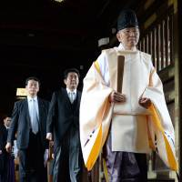 Prime Minister Shinzo Abe follows a Shinto priest at Yasukuni Shrine in Tokyo in December 2013. As Japan observes the 70th anniversary of its surrender in World War II, tensions between pacifist liberals and nationalistic conservatives in Japan are intensifying.   AFP-JIJI