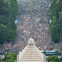 Thousands of demonstrators fill a street in front of the Diet building in Tokyo on Sunday during a rally protesting a pair of controversial security bills that will expand the scope of Japan's overseas military operations. An organizer claimed as many as 120,000 people participated in the massive demonstration. | KYODO
