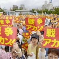 Protesters hold up banners reading 'No To War,' during a rally to protest against Prime Minister Shinzo Abe's drive to enact two controversial security bills on Sunday in Ogimachi Park in Osaka's Kita Ward. | KYODO