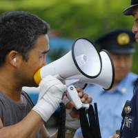 A protester uses a pair of megaphones to make his point during an anti-nuclear demonstration in Tokyo on Tuesday. | AP