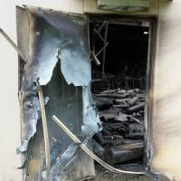 A damaged warehouse door is seen after a blast ripped through the building at the U.S. Army Sagami General Depot in Sagamihara, Kanagawa Prefecture, on Monday. | AFP-JIJI