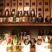 Sake bottles sit on a shelf at a bar in New York. Japanese sake brewers are stepping up U.S. production as it offers lower costs than exporting and quicker delivery. | BLOOMBERG