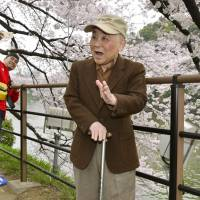 Eiichi Niihori, 82, who helped plant cherry trees along the Chidorigafuchi moat in Tokyo in the 1950s, recalls the aftermath of the war as he views the grown trees in full bloom in April. | KYODO
