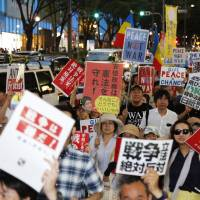 Members of SEALDs, a group of young people against government legislation allowing the Self-Defense Forces a greater role internationally, march in Tokyo's fashionable Omotesando district on Sunday. SEALDs stand for Students Emergency Action for Liberal Democracy.   KYODO