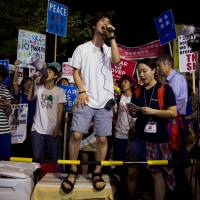 Aki Okuda (center), founding member of the protest group Students Emergency Action for Liberal Democracy (SEALDs), shouts slogans during a protest outside the Diet in Tokyo on Aug. 21. | REUTERS