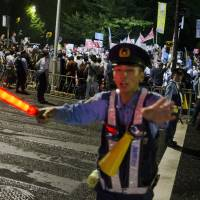 A police officer gestures as he keeps watch on a pedestrian crossing leading to a demonstration led by the protest group Students Emergency Action for Liberal Democracy (SEALDs) outside the Diet in Tokyo on Aug. 21. | REUTERS