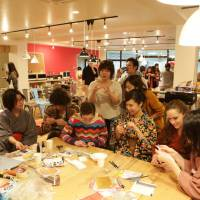 Residents at English-immersion share house Will Fuchu in Tokyo teach origami to non-Japanese guests at a sushi party in the common lounge in January 2015. | COURTESY OF IRODORI FACTORY