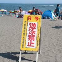 A 'no swimming' signboard stands at Chigasaki Southern Beach in Kanagawa Prefecture on Saturday. | KYODO