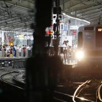 Train platforms are full of people waiting for service to resume Tuesday evening at Tokyu Jiyugaoka Station in Tokyo. Trouble with the signal-controlling system affected about 360,000 evening commuters. | KYODO