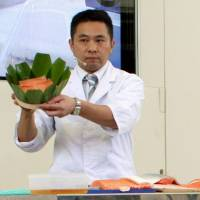 A Japanese chef talks about masuzushi, a local raw fish dish from Toyama Prefecture at the Japanese pavilion of Expo Milano 2015 in Milan, Italy, on Saturday. | KYODO