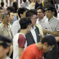 An official at JR Tachikawa Station explains to passengers the suspension of train services following a cable fire on Tuesday night. | KYODO