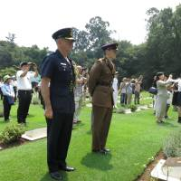 Group Capt. John Harwood (left), defense and armed services attache at the Australian Embassy in Tokyo, and Capt. Oliver Clark of the British Army, representing the British Embassy, attend the 21st annual memorial service in Yokohama on Saturday for POWs from the British Commonwealth and former Allied nations who died in Japan during World War II. | KAZUAKI NAGATA