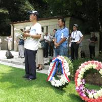 People attending the 21st memorial service held for POWs from the British Commonwealth and Allied nations who died in Japan during World War II sing at the event in Yokohama on Saturday. | KAZUAKI NAGATA