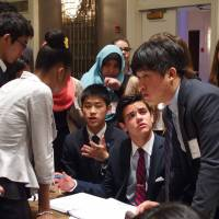 High school student Takumi Masaka (third from left, seated) chats with students from other countries at the Global Classrooms International High School Model U.N. Conference, held in New York in May. | COURTESY OF ASIA-PACIFIC CULTURAL CENTRE FOR UNESCO / KYODO