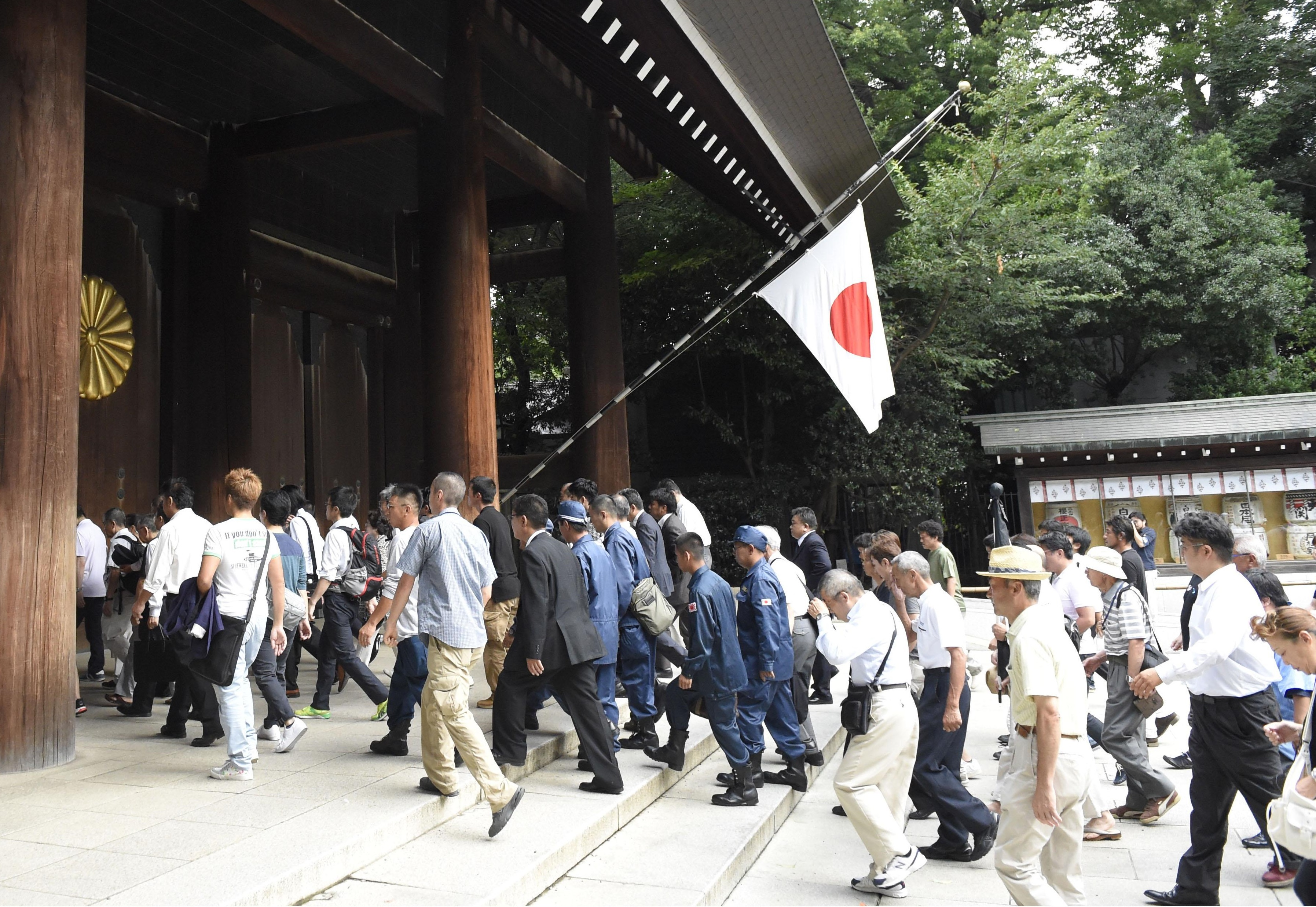 People enter Yasukuni Shrine in Tokyo Saturday morning to honor the nation's war dead on the 70th anniversary of the end of World War II. | KYODO